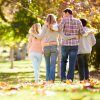 Rear View Of Family Walking Through Autumn Woodland With Arms Around Each Other