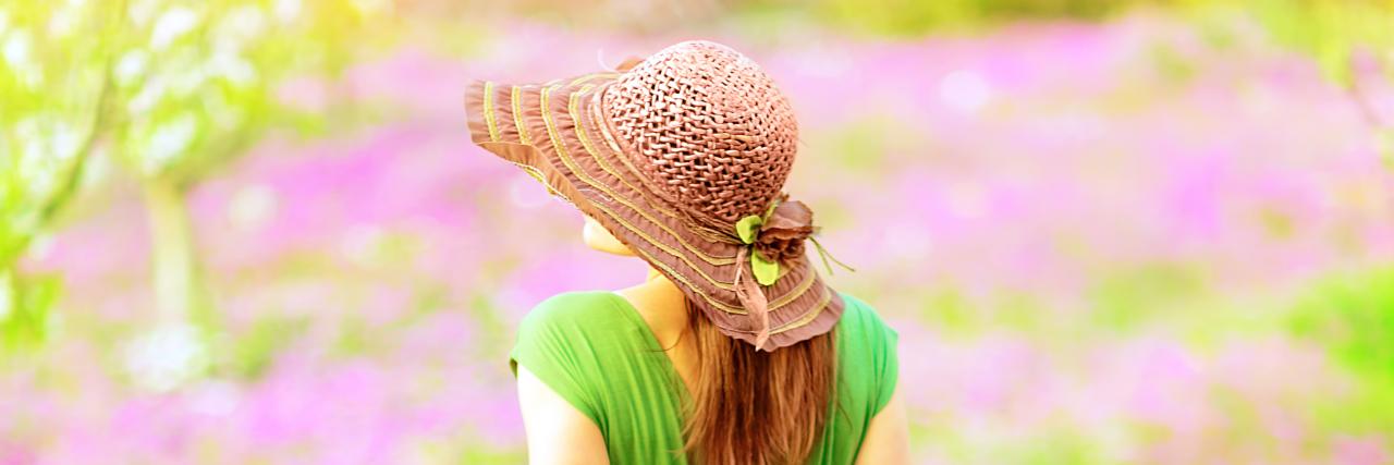 Woman walking in spring garden.