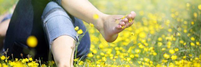 woman lying in meadow of buttercups barefoot