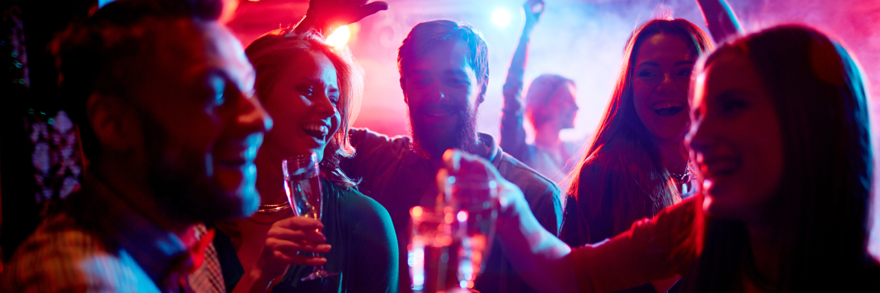 Group of young people celebrating with drinks in nightclub.