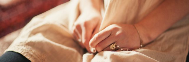 A photo of a woman's hands fidgeting with her dress.