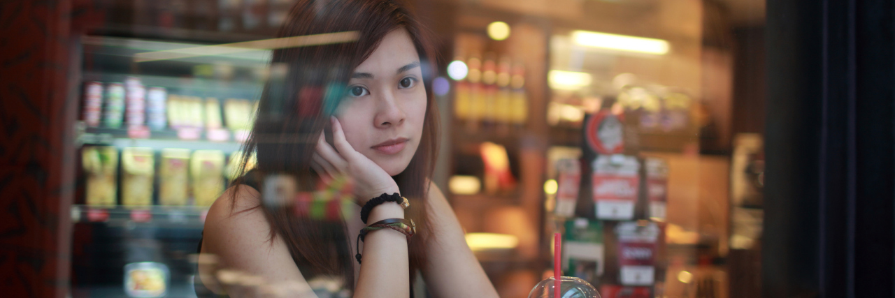 young woman in cafe at night with depression looking out of window