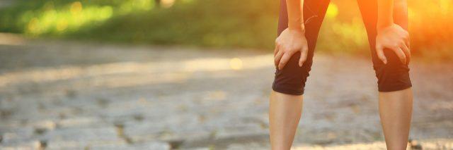 female runner resting her hands on her knees
