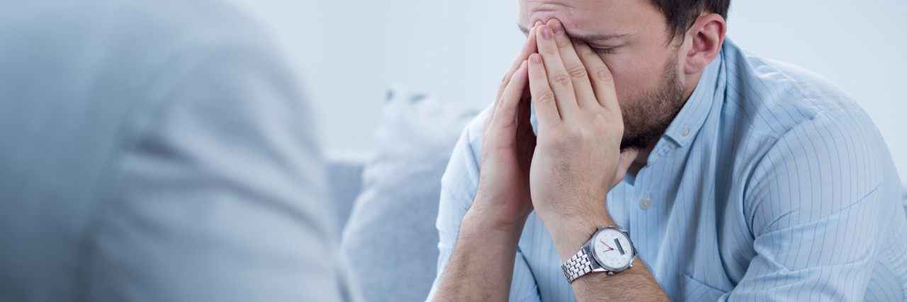 man crying during therapy session