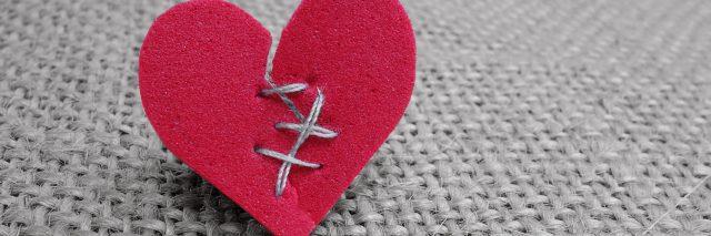 Broken red heart with white thread stitches