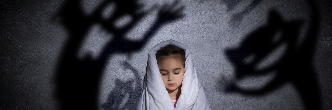 little girl hiding under blanket from monsters