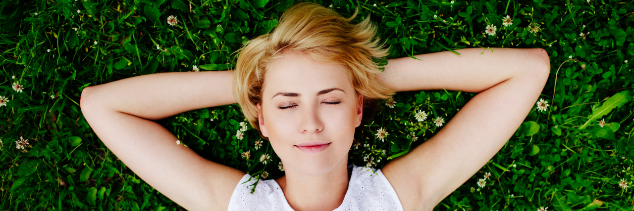 Portrait of a young woman lying on the grass