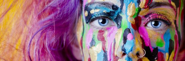 A close-up of a woman with paint on her face.
