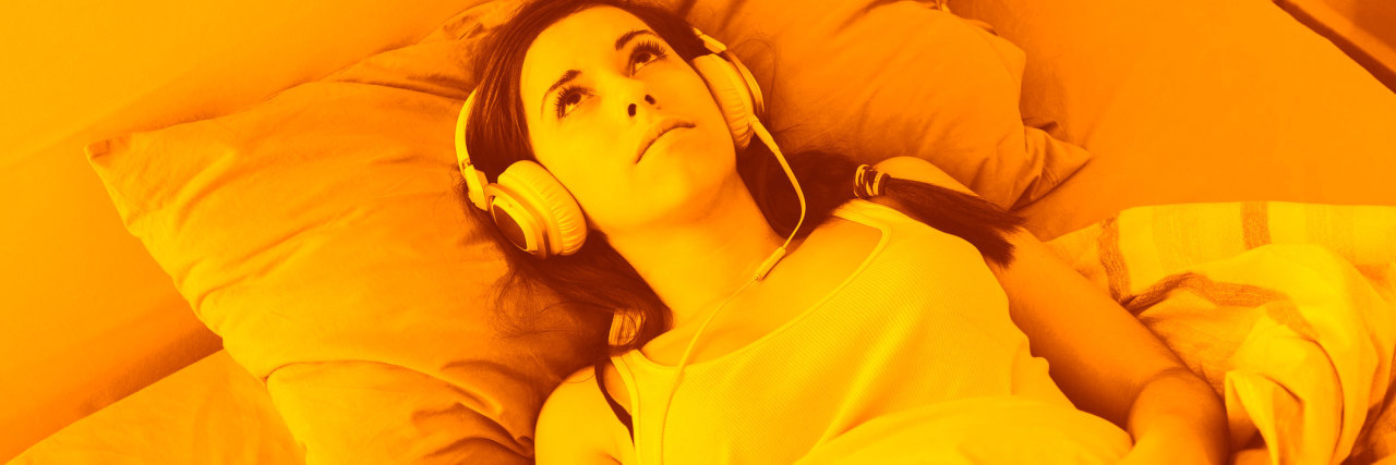 Young Woman Listening Music with Headphones on the Bed. She is Alone, wearing a white Undershirt. The bed has green and orange Sheets. She is Lying down, Looking at Ceiling with a Sad Expression.