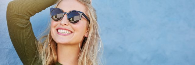 woman with blonde hair smiling and wearing sunglasses against a blue wall