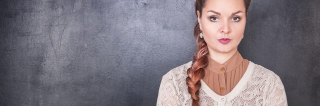 woman with long hair in a braid standing against a wall with her arms crossed