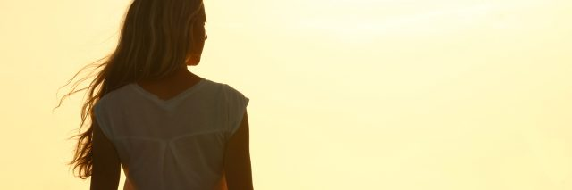 young woman watching sunset silhouette from behind