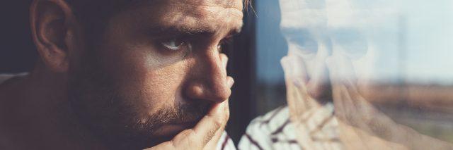 Sad young man looking through window.