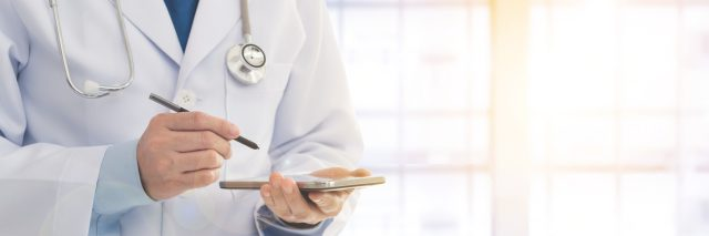 doctor writing on tablet