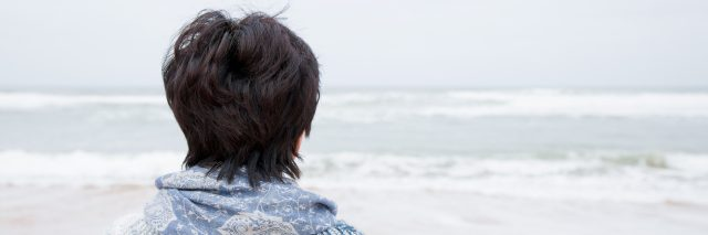 woman standing on the beach and wrapped in a blue knit blanket