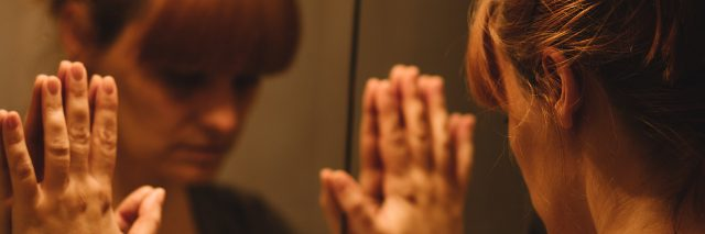 woman with her hands against the mirror looking at her reflection