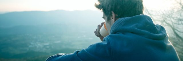 man drinking coffee looking at view