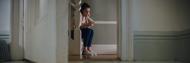 A teenage girl sitting on a staircase looking at her phone.