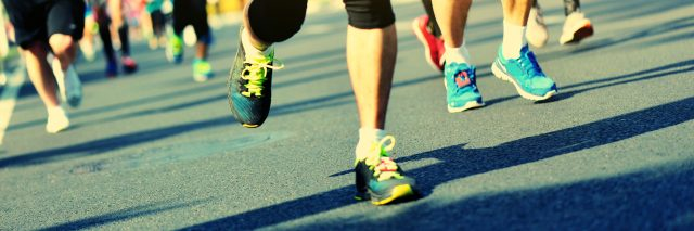 legs and feet of people running a race