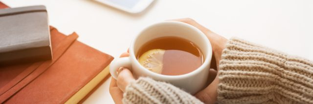 Close up of woman hands holding a cup of lemon tea on white table in a winter afternoon. Woman
