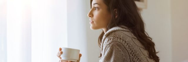 dark haired woman looking out window with coffee