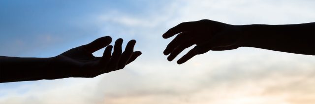 Two hands reaching to help each other, silhouette on sky background.