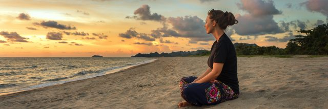 Woman sitting on beach sand and relaxing at sunset.