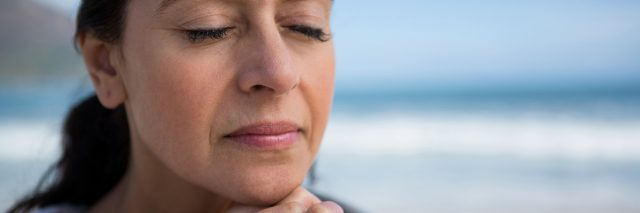 Mature woman praying with hands clasped on beach