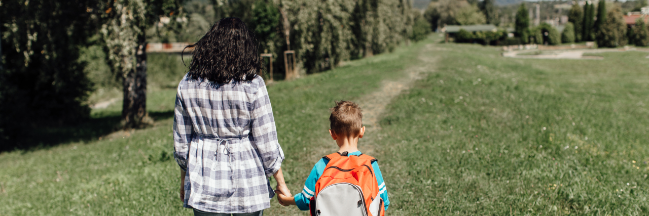 Mother and son walking through grassy field.