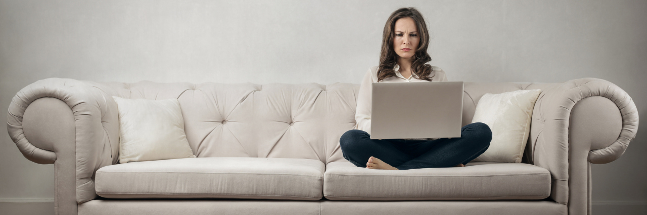 woman working on computer on couch