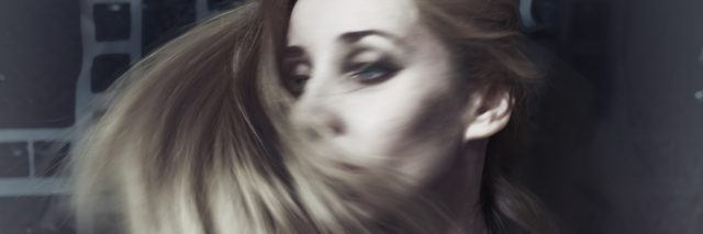 blurred motion of a blonde woman swishing her hair around her face