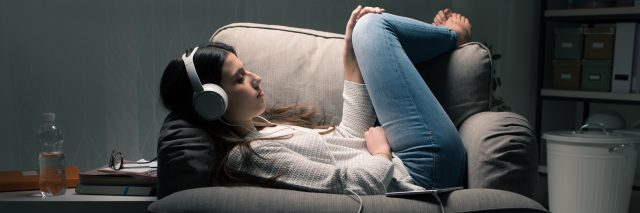 young woman headphones at night curled up on chair