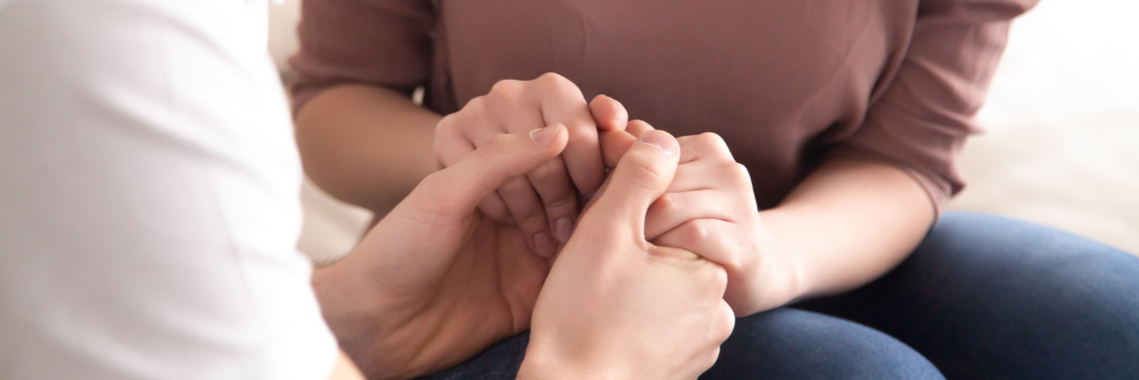 man and woman holding hands comforting support