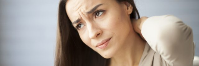 woman with worried expression holding back or neck
