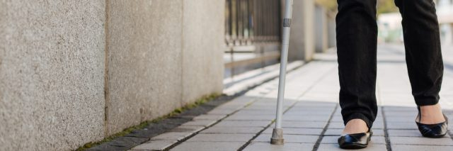 Woman walking along the avenue with crutches.