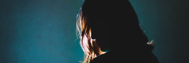 silhouette of sad woman standing in the dark with light shine behind