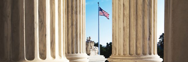 The marble columns of the Supreme Court of the United States in Washington DC, with the American flag in the background