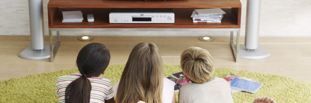 Three young kids watching television.