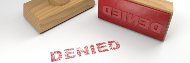 Two rubber stamps with the word denied and a stamp on white background.