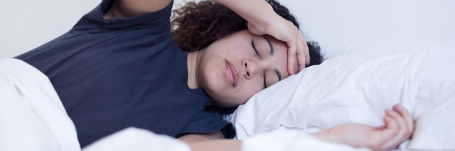 woman lying in bed with headache or depression