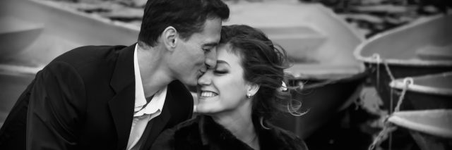 black and white photo of a couple kissing on a boat