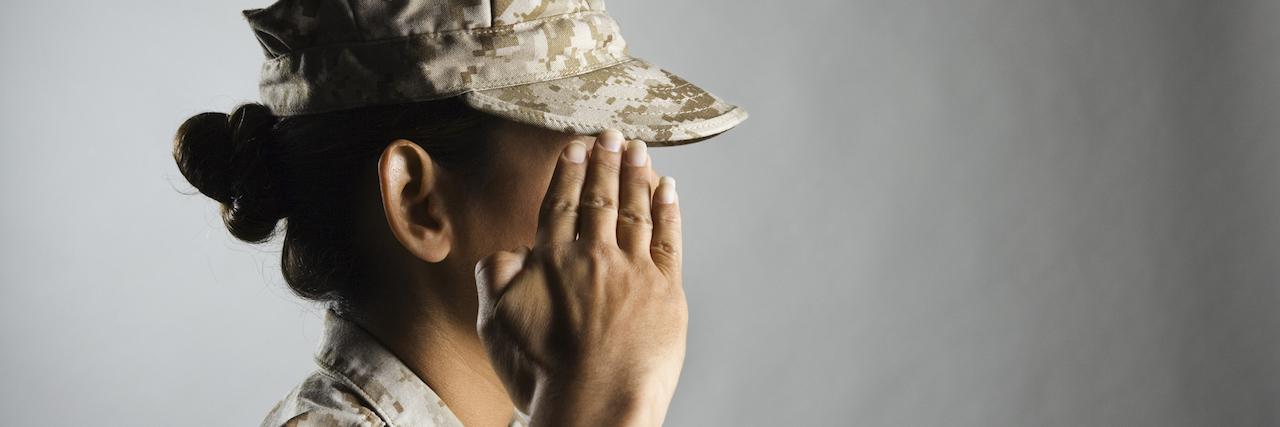 A woman in uniform saluting