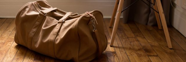 A duffle back by a white chair.