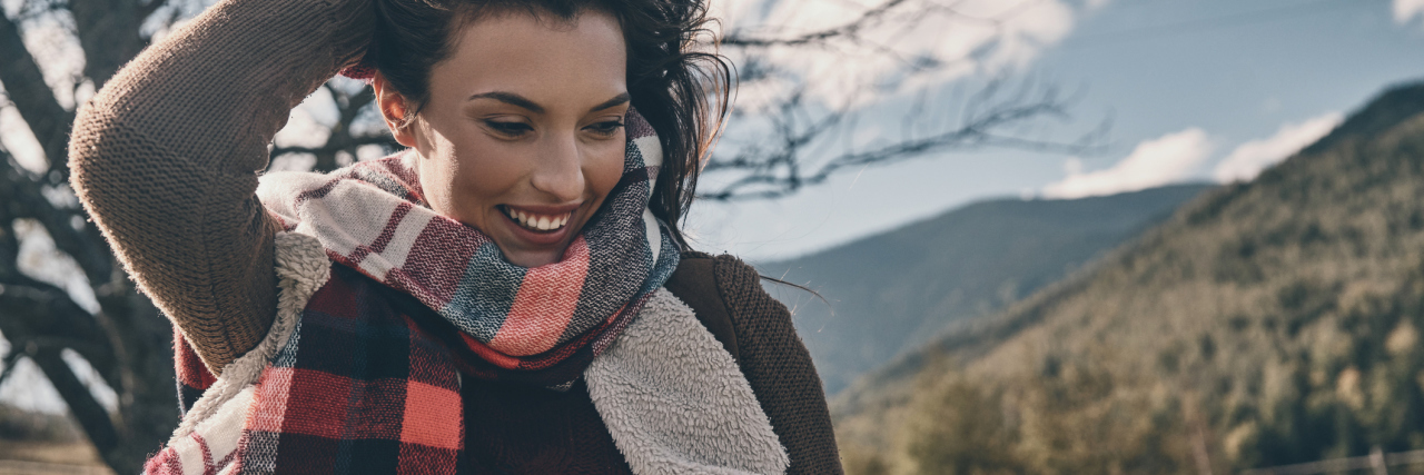 woman wearing a scarf and jacket standing outside smiling and running her fingers through her hair