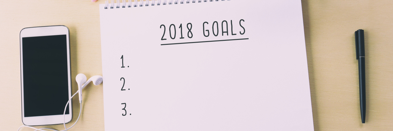 """notepad saying """"2018 goals"""" on a table with a pair of glasses and a glass of coffee"""