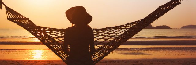 Woman in hammock enjoying sunrise.