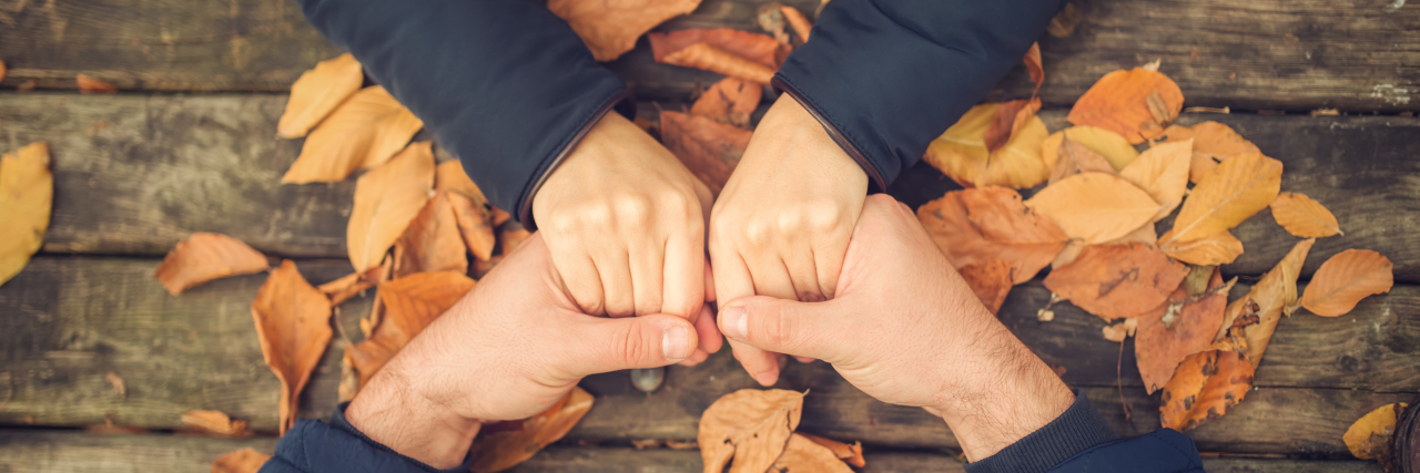 photo of two hands holding another's on a table with leaves.