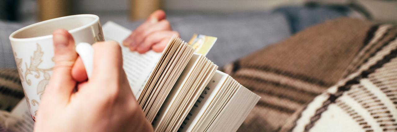 woman holding a book and a mug of tea
