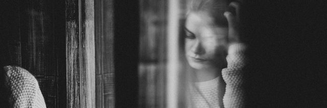 black and white reflection of a girl reading on a window sill
