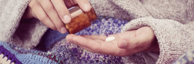 person wrapped in a blanket and pouring a pill from a bottle into their hand